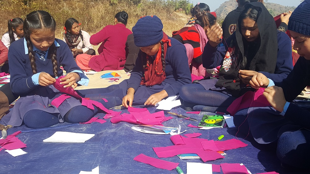 School girls sewing outside.